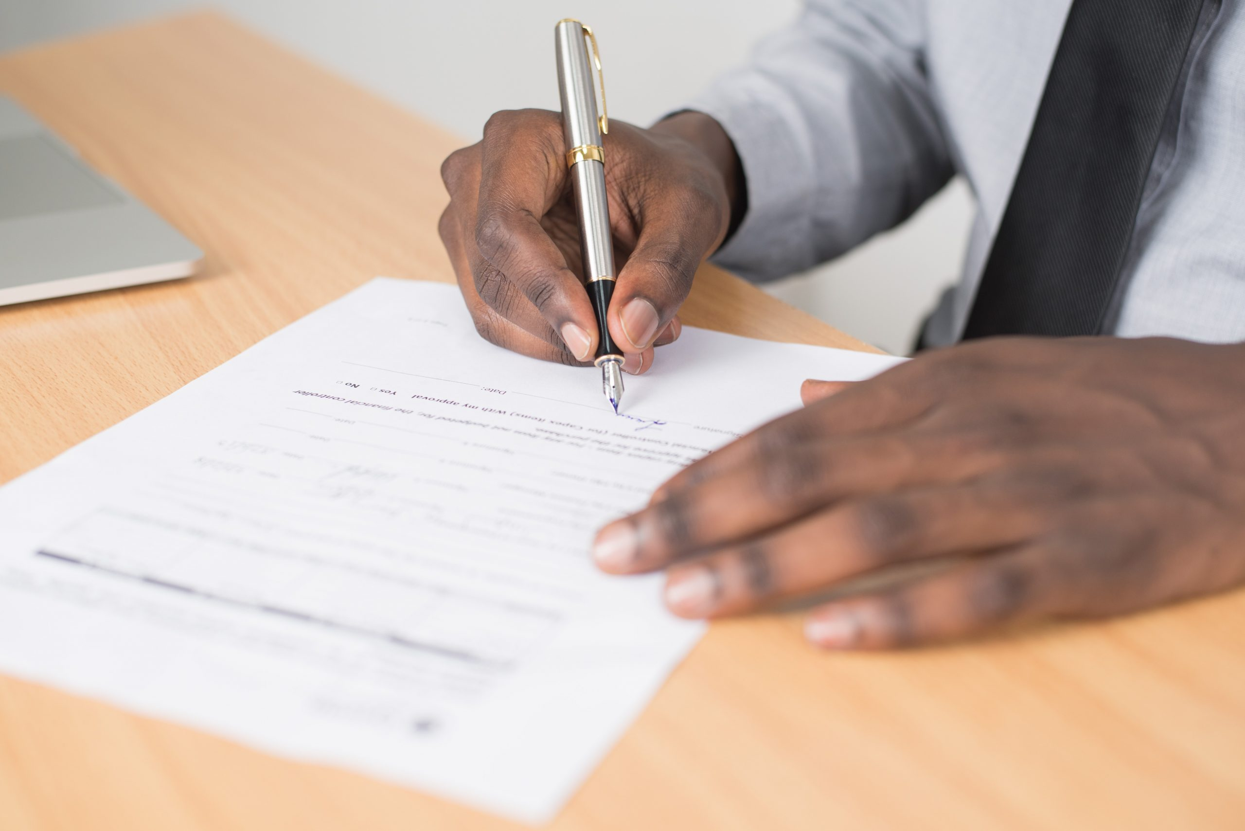Man in tie signing documents
