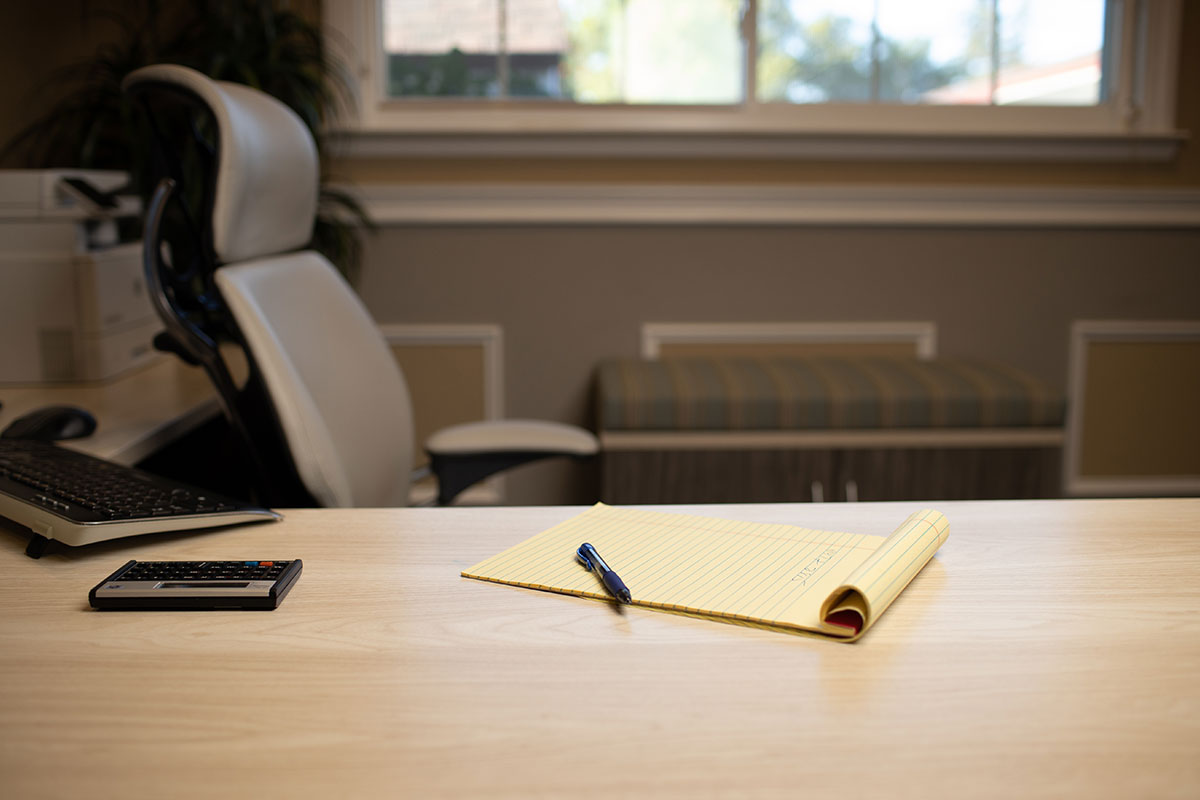 Pen and Notepad on Desk in Office